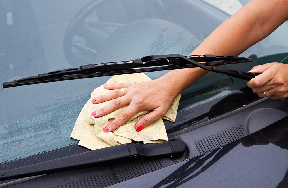 Woman cleaning windshield by hand